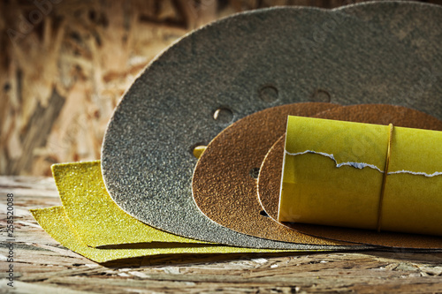 Photo abrasives round square and rolled  sheets of sandpaper on plywoo