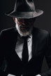 Old-aged bearded man in image of English secret agent wearing black suit with hat on his eyes posing against dark background.
