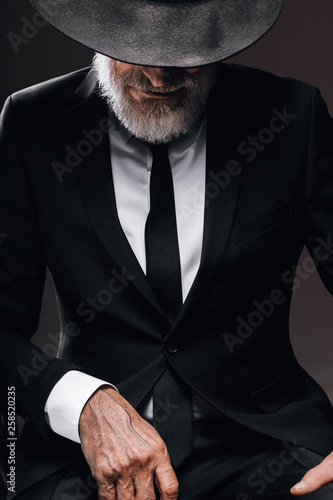 Fototapeta  Old-aged bearded man in image of English secret agent wearing black suit with hat on his eyes posing against dark background