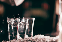 Close Up Photo Of Three Transparent Clean Short Glasses With Beverage Isolate On Dark Blurred Background.