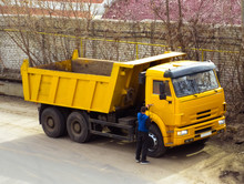 The Driver Next To The Industrial Yellow Truck