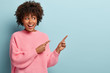Horizontal shot of positive lovely woman with Afro haircut, points away with both fore fingers, demonstrates copy space for your information, has appealing look, sincere smile on face. Advertisement