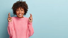 Portrait Of Happy Smiling Lady Has Broad Shining Smile, Crosses Fingers, Believes In Good Luck, Being In Good Mood, Wears Oversized Pink Jumper, Isolated Over Blue Backround. Body Language Concept