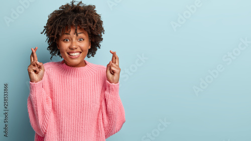 Portrait of happy smiling lady has broad shining smile, crosses fingers, believes in good luck, being in good mood, wears oversized pink jumper, isolated over blue backround Wallpaper Mural