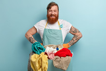 Positive Red Haired Housekeeper Glad To Finish Domestic Work, Keeps Hand On Waist, Wears Casual T Shirt And Apron, Prepares For Washing Linen, Poses Over Blue Background. Laundry Day Concept