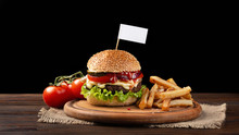 Homemade Hamburger Close-up With Beef, Tomato, Lettuce, Cheese And French Fries On Cutting Board. Small White Flag Inserted In The Burger