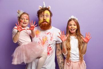 Funny stupefied dad and two adorable daughters show dirty palms with paints, stare at camera together, wear festive carnival costumes, celebrate Children Day, isolated over purple background