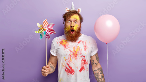 Obraz Indoor shot of surprised red man stares with shock, holds balloon and windmill in both hands, wears unicorn headband with horn and ears, smearked with colorful paints, entertains children on party - fototapety do salonu