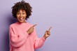 canvas print picture - Waist up shot of positive lovely woman with Afro hairstyle, points away with both fore fingers, shows somethig on blank space, has joy expression, wears loose pink jumper, gestures over violet wall