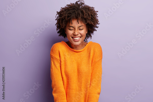 Fotografie, Obraz  Candid shot of attractive Afro American woman laughs happily, keeps eyes shut fr