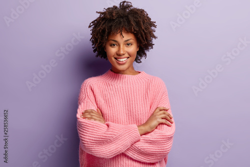 Fotomural Photo of self confident pleased dark skinned woman keeps arms folded, smiles gladfully while watches funny programme, has natural appealing beauty, wears oversized pink jumper, poses indoor