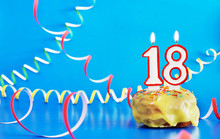 Birthday Of Eighteen Years. Cupcake With White Burning Candle In The Form Of Number 18. Vivid Blue Background With Copy Space