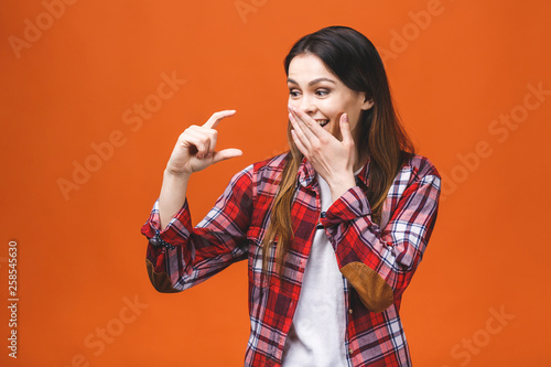Photo  Portrait of smiling woman showing small amount of something, isolated against orange background