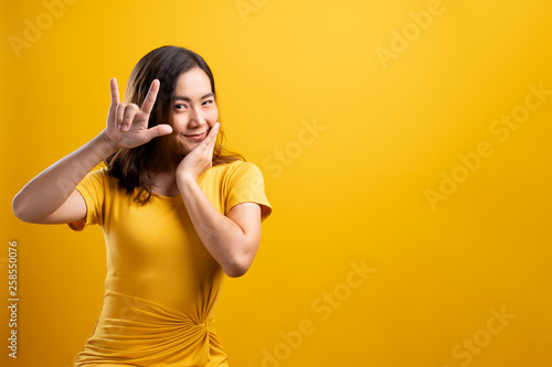 Valokuvatapetti Woman in love showing heart isolated over yellow background