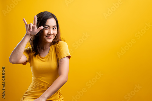 Valokuva  Woman in love showing heart isolated over yellow background