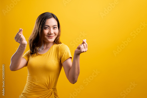 Fotografija  Woman in love showing heart isolated over yellow background