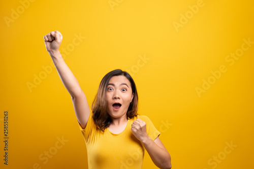 Happy woman make winning gesture isolated over yellow background Canvas Print