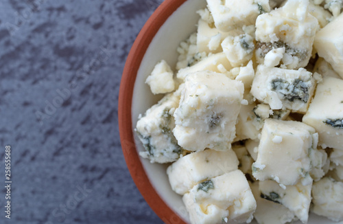 Photo Portion of crumbled blue cheese on a in a small bowl atop a gray background top