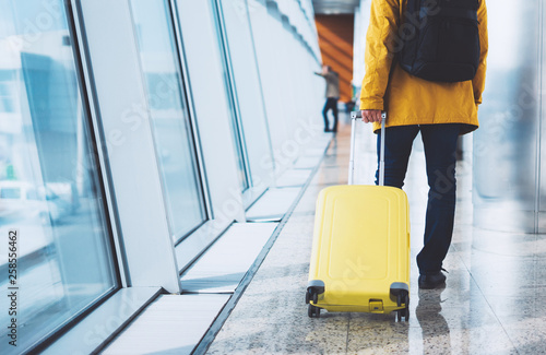 traveler tourist with yellow suitcase backpack at airport on background window b Fotobehang