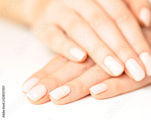 Staande foto Manicure Female hands with smooth skin and stylish pink manicure.