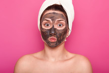 Close Up Shot Of Beautiful Female, Has Chocolate Mask On Face, Keeps Eyes Wide Opened And Lips Rounded, Poses With Naked Body, Has White Towel On Head, Having Rest In Spa Salon, Isolated On Pink Wall.
