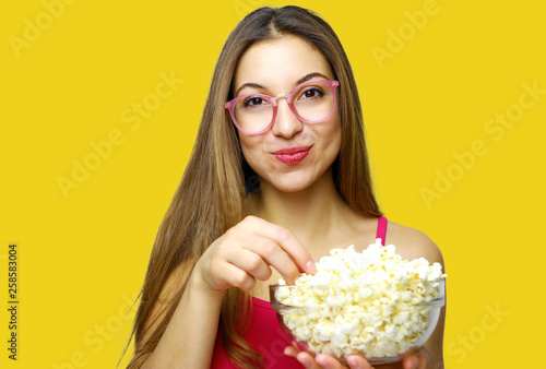 Photo  Girl with positive emotion holding pop corn and watching comedy movie isolated o