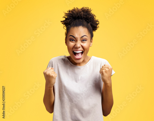 Photo  Excited girl with widely open mouth holds hands clenched in fists, exclaimed with positiveness