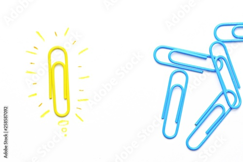 Fotografía  A yellow paper clip as a symbol of a light bulb that radiates lies on a white su