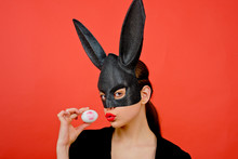 Easter Woman. Woman Rabbit, Easter Bunny Girl. Red Lip Imprint On Easter Egg On Red Background. Female Mouth Kiss. Print Of Red Lips On White Egg.