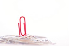 A Red Paperclip Stands In A Heap Of Silver Nondescript Paper Clips - Abstract And Symbolic Representation Of An Individual In Business Life Setting Himself Apart From Others