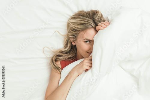 Fototapeta Happy Caucasian Blonde Girl Peeking from Under White Duvet Covers obraz
