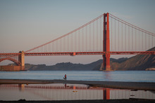 Golden Gate Bridge, Early Morning.  Woman Walking A Dog On The Beach In Foreground.