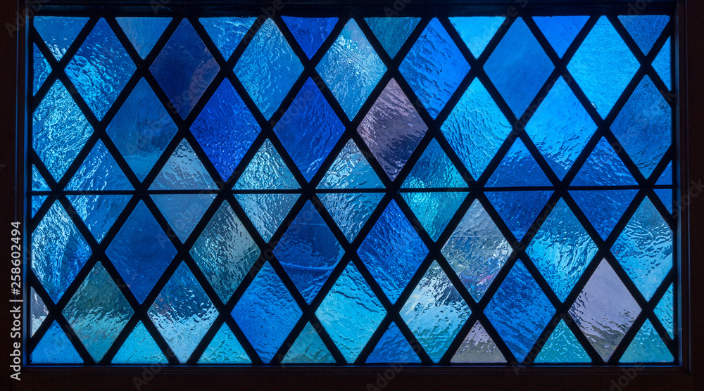 Fotografía  Detail of blue diamond shaped panes in colored light from stained glass window i