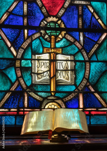 Photo  Colored light from stained glass window in methodist church falls across open bi