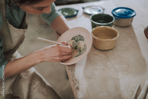 Young lady in apron painting ceramic plate at workshop Fototapet