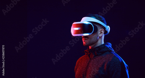 Fototapeta Model young man with beard in glasses of virtual reality on dark background.. Augmented reality, science, future technology concept. VR. Futuristic 3d glasses with virtual projection. Neon light. obraz