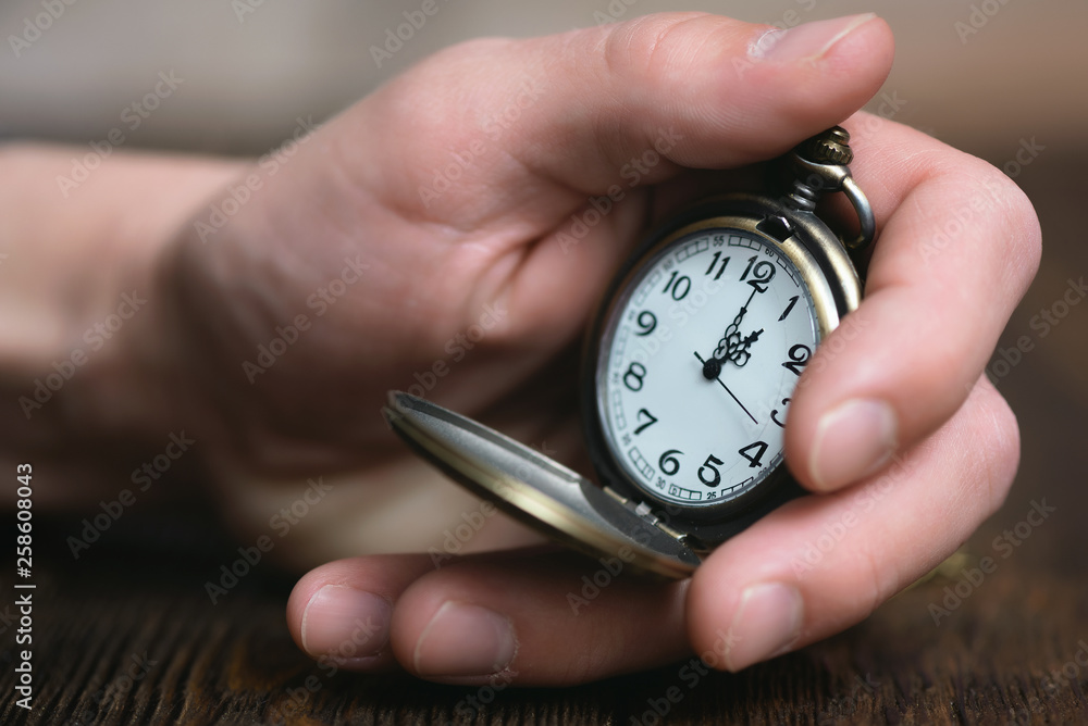 Fototapeta Man is holding in hand a pocket watch on a brown table background.