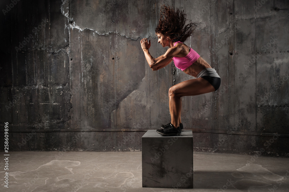 Fototapety, obrazy: Fit young woman box jumping at a crossfit style on gray background. Fitness, crossfit, functional, training, and lifestyle concept