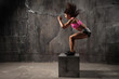 Fit young woman box jumping at a crossfit style on gray background. Fitness, crossfit, functional, training, and lifestyle concept