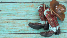 Cowboy Boots And Hat Laying On A Teal Background