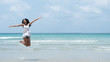 Beautiful young Asian woman are jumping and show hand in to sky relaxing on beach on summer holidays vacations. Concept freedom, Lifestyle, tourism, holiday. with copy space
