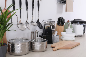 Set of clean cookware, dishes, utensils and appliances on table at white wall