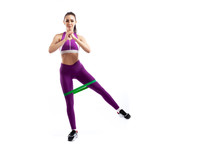 A Ypung Woman Coach In A Sporty Pink   Short Top And Gym Leggings Makes Lunges  By The Feet Forward With Sport Fitness Rubber Bands,  Stretch Legs On A  White Isolated Background In Studio