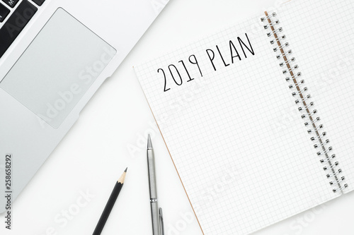 Photo  Notebook with 2019 plan text is on top of white office desk table