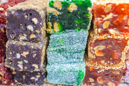 Fotografia  Multicolored bars Turkish delight rakat with nuts oriental sweets, soft selective focus