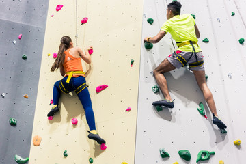 Sporty people climbing wall