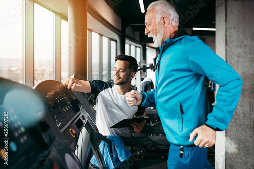 Senior and young sportsmen exercising at gym.