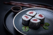 maki sushi raw tuna nori seaweed with soy sauce and chopsticks on a dark plate