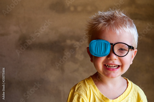 Fotografía Portrait of funny child in new glasses with patch for correcting squint