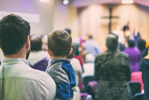 Vászonkép Father with his son participate at christian congregation worship